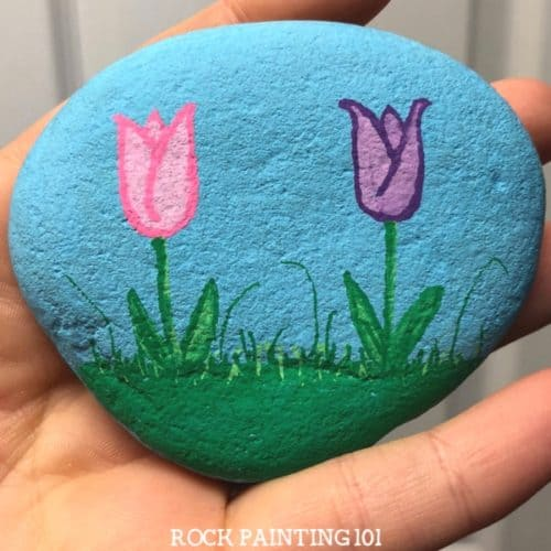 These tulip painted rocks are the perfect rock painting idea for spring! Learn how to draw a tulip while creating a rock that's perfect for hiding, gifting, or decorating!