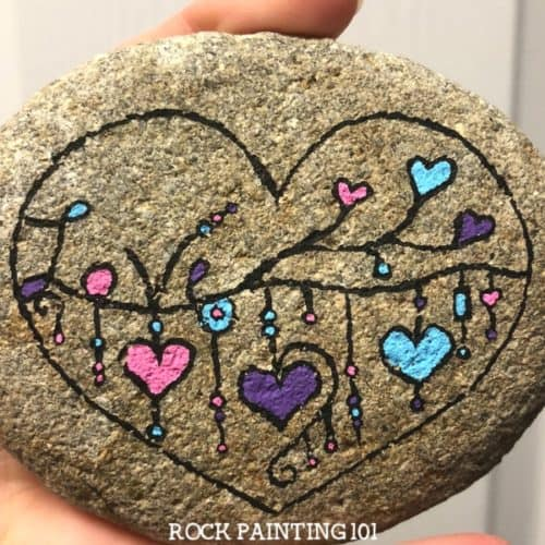 This dangle heart painted rock is so much fun and perfect for hiding, gifting, or keeping! The zendangle style is a great technique for beginners.