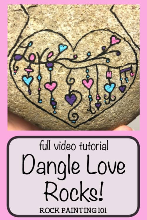 This dangle heart painted rock is so much fun and perfect for hiding, gifting, or keeping! The zendangle style is a great technique for beginners.#heartrocks #dangleheartpaintedrocks #loverocks #zendangle #heartpaintingideas #stonepaintingideas #rockpaintingforbeginners #howtopaintrocks #rockpainting101