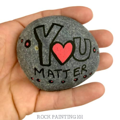 Are you participating in International Drop A Rock Day? Check out all the fun details about this fun day that takes rock hunting to a new level by spreading love and kindness around the world. #internationaldroparockday #droparock #kindnessrocks #youmatter #redheart #howtopaintrocks #rockpainting101