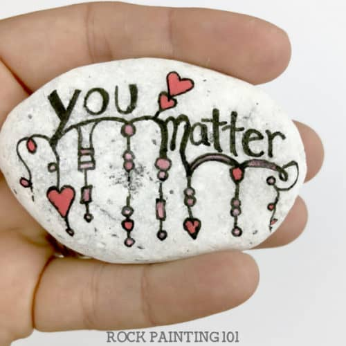 Are you participating in International Drop A Rock Day? Check out all the fun details about this fun day that takes rock hunting to a new level by spreading love and kindness around the world. #internationaldroparockday #droparock #kindnessrocks #youmatter #redheart #howtopaintrocks #zendangle #dangle #rockpainting101