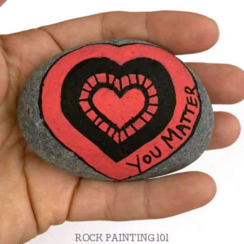 Are you participating in International Drop A Rock Day? Check out all the fun details about this fun day that takes rock hunting to a new level by spreading love and kindness around the world. #internationaldroparockday #droparock #kindnessrocks #youmatter #redheart #howtopaintrocks #heartrocks #rockpainting101