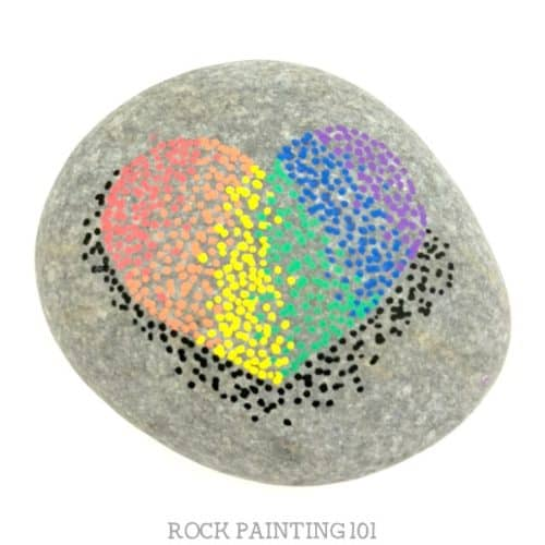 These rainbow pointillism heart rocks are beautiful and fun to create. They are perfect for people who love the dot painting look but don't have the steady hand for its perfection. #rainbow #pointillism #rockart #heartrock #paintedrocks #rockpaintingforbeginners #stonepainting #rockpainting101