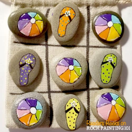 Maketic tac toe rocks that are the perfect boredom buster for kids. They also make amazing gifts! Check out the video tutorial and a collection of ideas for your set. #tictactoe #rocks #travelgame #rockpaintingideas #rockgames #rockgifts #sandals #flipflops #beachball #summer #rockpainting101