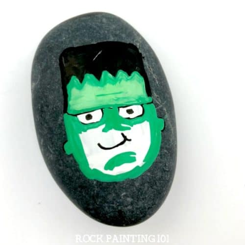 Paint a Frankenstein's monster for a spooky and fun Halloween rock painting idea. He's cute and creepy and perfect for kids to find while their trick or treating! #frankenstein #frankentsteinsmonster #halloweenrockpaintingideas #halloween #stonepainting #monsterrocks #howtopaintrocks #howtodraw #rockpainting101
