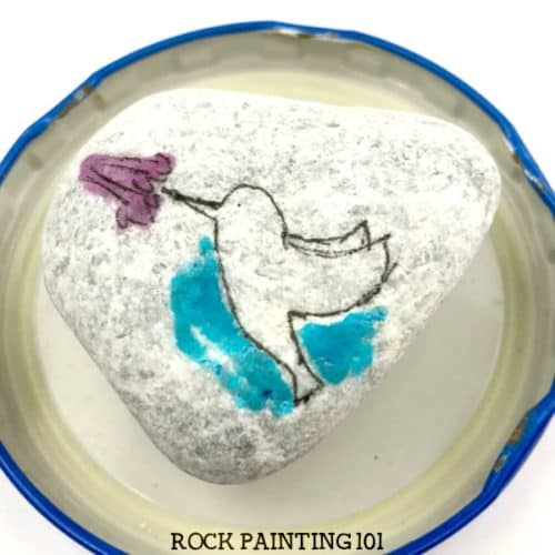 Paint a beautiful hummingbird using a simple technique. Create the look of watercolors without the difficulty and you'll paint a beautiful rock. #watercolor #hummingbird #howtopaintrocks #stonepainting #paintedrocks #rockart #howtopaint #rockpainting101