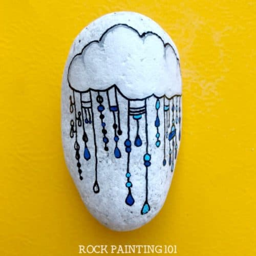 This fun raincloud zendangle painted rock is a great rock painting idea for beginners or for those looking to improve their skill. #zendangle #raincloud #kindnessrocks #rockpainting #paintedrocks #rockart #howtozendangle #dangles #rockpainting101