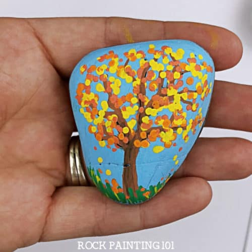Learn how to use dot painting to make beautiful fall tree painted rocks. This beginner's rock painting idea is perfect for hiding around your neighborhood this fall! #dotpainting #falltree #fallrocks #stonepainting #paintedrocks #howtopainttrees #rockpainting101