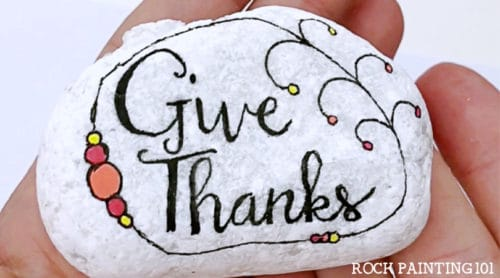 Make beautiful hand lettered Thanksgiving rocks with this step by step tutorial. Hand lettering has always been hard for me, but these practice sheets are perfect for learning! #handlettering #thanksgivingrocks #givethanks #howtohandletter #kindnessrocks #thanksgivingrockpainting #howtopaintrocks #rockpainting101