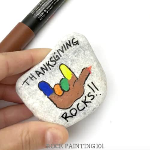 This fun Thanksgiving Rocks turkey painted rock is perfect for giving this holiday season. Brighten someone's day or use it to decorate your holiday table. It's a quick and simple video tutorial. #thanksgivingrocks #turkey #paintedrock #thanksgivingrockpaintingideas #stonepainting #rockart #thanksgivingdecor #thanksgivingcraft #rockpainting101