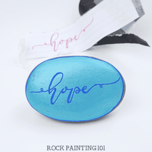 How to use carbon paper to hand letter on rocks. Using this simple supply and practice sheets, you will be hand lettering your painted rocks like a pro! #handlettering #carbonpaper #easy #tutorial #kindnessrocks #holidayrocks #hope #howtopaintrocks #rockart #paintedrocks #rockpainting101