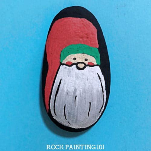This Christmas gnome rock painting idea is a fun way to paint rocks during the holidays. Learn how to draw a gnome onto a rock with step by step instructions and a video tutorial. #christmasgnome #holidaygnome #christmasrocks #howtodrawagnome #holidayrockpainting #rockpainting101