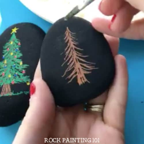 Learn how to paint a Christmas tree for fun holiday rocks. Watch the video tutorial and see just how easy these Christmas stones are to create. They are perfect for stocking stuffers, hiding this winter, or giving to a friend! #christmastree #christmasrockpainting #howtopaintachristmastree #rockpaintingforbeginners #rockart #stonepainting #stockingstuffers #rockpainting101