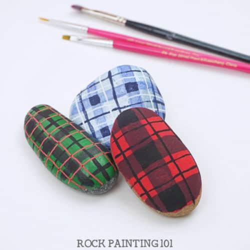 Learn how to paint plaid patterns with these step by step instructions and video tutorial. We used it to paint a fun Christmas rock, but you can use it for any project you have! #plaid #howtopaintplaid #flannel #red #christmasflannel #howtopaintrocks #christmasrockpaintingidea #tutorial #stonepainting #stockingstuffers #holidayrockhunting #giftideas #rockpainting101