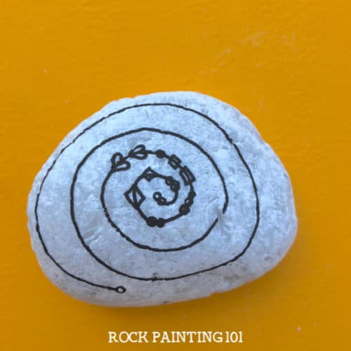This spiral zendangle rock painting idea is a fun twist on a typical dangle painted rock. Perfect for giving to loved ones or hiding in your city. #spiralzendangle #zendangle #dangles #howtozendangle #rockpaintingideas #love #rockpainting101