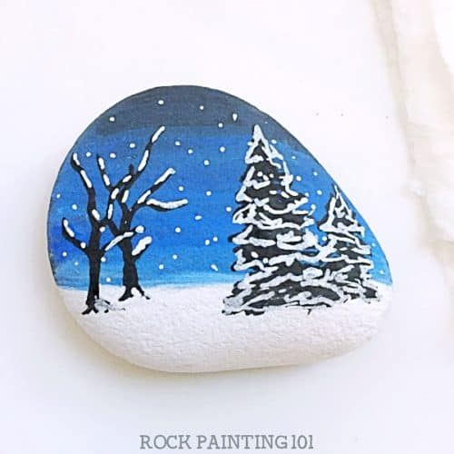 Awinter scene rock painting idea is perfect for hiding during these cold winter days. They also make fantastic winter decorations and gift. Practice your blending skills and break out your paint pens, this stone painting tutorial is perfect for all skill levels. #rockpainting101
