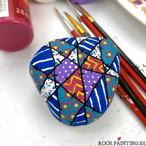 Colorful winter quilt pattern painted on a rock.