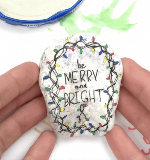 outlining and painting Christmas lights on the rock