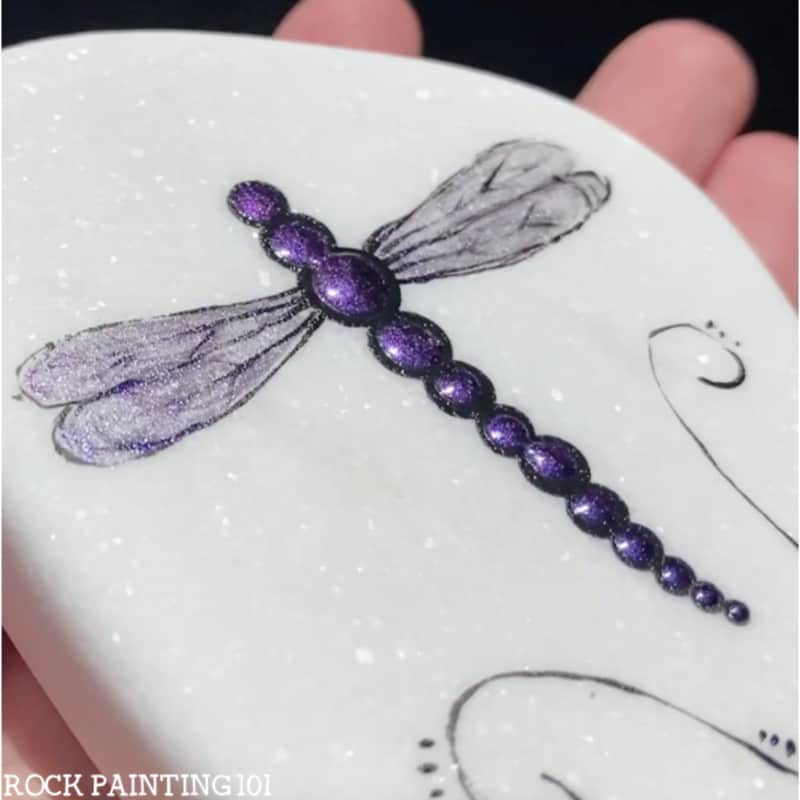 In today's tutorial we are teaching you how to paint dragonfly rocks. This tutorial is perfect for the rock painting beginner and features a beautiful color shift paint from Naturalis Paint that really makes these dragonflies sparkle!